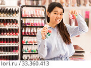 Купить «Asian woman holding nail varnish bottles», фото № 33360413, снято 24 октября 2019 г. (c) Яков Филимонов / Фотобанк Лори