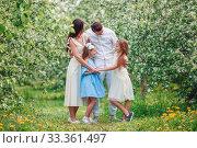 Купить «Adorable family in blooming cherry garden on beautiful spring day», фото № 33361497, снято 16 мая 2018 г. (c) Дмитрий Травников / Фотобанк Лори