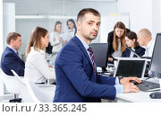 Купить «Confident businessman concentrated on work with laptop in coworking space», фото № 33365245, снято 21 апреля 2018 г. (c) Яков Филимонов / Фотобанк Лори