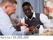 Купить «Cheerful African talking with friend at home, using phone», фото № 33365269, снято 26 февраля 2018 г. (c) Яков Филимонов / Фотобанк Лори