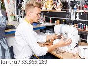Tailor working with sewing machine at atelier. Стоковое фото, фотограф Яков Филимонов / Фотобанк Лори