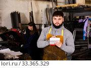 Купить «Proffessional young man engineer taking notes in notebook», фото № 33365329, снято 5 апреля 2020 г. (c) Яков Филимонов / Фотобанк Лори