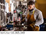 Купить «Professional man worker during work with steel in workshop», фото № 33365349, снято 5 апреля 2020 г. (c) Яков Филимонов / Фотобанк Лори