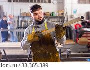 Metalworker checking metal structures. Стоковое фото, фотограф Яков Филимонов / Фотобанк Лори