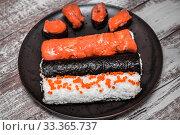 Купить «Various kinds of sushi served on dark plate macro», фото № 33365737, снято 11 марта 2020 г. (c) katalinks / Фотобанк Лори