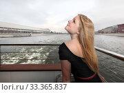 Красивая блондинка в профиль и  в черном платье на корабле в городе. Ветер на реке (2011 год). Стоковое фото, фотограф Elizaveta Kharicheva / Фотобанк Лори