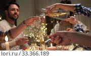 Купить «happy friends having christmas dinner at home», видеоролик № 33366189, снято 9 февраля 2020 г. (c) Syda Productions / Фотобанк Лори