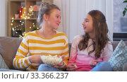 Купить «teenage girls eating popcorn at home», видеоролик № 33366237, снято 18 января 2020 г. (c) Syda Productions / Фотобанк Лори
