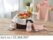 Купить «teddy bear toy in basket with baby things on table», фото № 33368997, снято 14 февраля 2019 г. (c) Syda Productions / Фотобанк Лори
