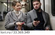 Купить «Man and woman using phone inside subway», видеоролик № 33369349, снято 11 ноября 2019 г. (c) Яков Филимонов / Фотобанк Лори