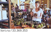 Young positive woman choosing ceramic products in pottery store. Стоковое видео, видеограф Яков Филимонов / Фотобанк Лори
