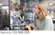Stylish female client choosing elegant necklace from natural pearls in jewelry shop. Стоковое видео, видеограф Яков Филимонов / Фотобанк Лори