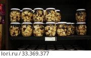 Купить «Glass jars with assorted preserved mushrooms on shelves in store», видеоролик № 33369377, снято 5 июля 2020 г. (c) Яков Филимонов / Фотобанк Лори