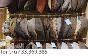 Купить «Large assortment of flat caps hanging on showcase in clothes shop», видеоролик № 33369385, снято 2 апреля 2020 г. (c) Яков Филимонов / Фотобанк Лори