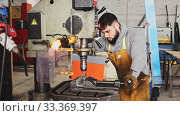 Купить «Craftsman working on metal structures drilling machine», видеоролик № 33369397, снято 30 мая 2020 г. (c) Яков Филимонов / Фотобанк Лори