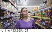 Купить «Woman is walking glad during shopping in modern supermarket», видеоролик № 33369405, снято 11 июля 2020 г. (c) Яков Филимонов / Фотобанк Лори