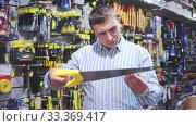 Купить «Male customer choose bucksaw at hardware store», видеоролик № 33369417, снято 8 апреля 2020 г. (c) Яков Филимонов / Фотобанк Лори