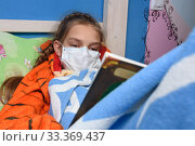 Teenage girl lies in medical mask in bed and reads book. Стоковое фото, фотограф Иванов Алексей / Фотобанк Лори