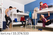 Купить «Young men and women friendly interacting while staying in modern comfy hostel», фото № 33374533, снято 22 марта 2018 г. (c) Яков Филимонов / Фотобанк Лори