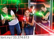 Купить «First person view of young people aiming from laser gun in dark», фото № 33374613, снято 27 августа 2018 г. (c) Яков Филимонов / Фотобанк Лори