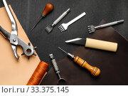 Leather crafting DIY tools lies on natural black and brown leather. Стоковое фото, фотограф Бражников Андрей / Фотобанк Лори