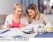 Daughter helps mother to lead home accounting. Стоковое фото, фотограф Яков Филимонов / Фотобанк Лори