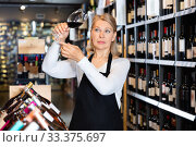 Купить «Focused mature woman wine producer inspecting quality of wine in wineshop on background with shelves of wine bottles», фото № 33375697, снято 6 июля 2020 г. (c) Яков Филимонов / Фотобанк Лори