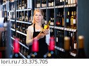 Купить «Smiling qualified mature saleswoman offering natural wines in bottles for sale at winery», фото № 33375705, снято 6 июня 2020 г. (c) Яков Филимонов / Фотобанк Лори