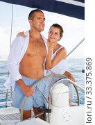 Купить «Couple standing at yacht wheel along coast of Barcelona», фото № 33375869, снято 6 апреля 2020 г. (c) Яков Филимонов / Фотобанк Лори