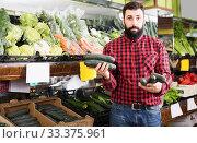 Купить «Man seller holding cucumbers in grocery store», фото № 33375961, снято 15 ноября 2016 г. (c) Яков Филимонов / Фотобанк Лори