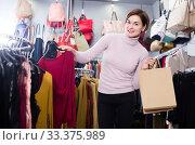 Купить «Cheerful female deciding on pretty blouse», фото № 33375989, снято 7 февраля 2017 г. (c) Яков Филимонов / Фотобанк Лори