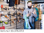 Купить «Guy is considering the range of climbing equipment», фото № 33376013, снято 24 февраля 2017 г. (c) Яков Филимонов / Фотобанк Лори