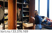 Купить «Anonymous lady taking photo of clothes in wardrobe», видеоролик № 33376169, снято 12 марта 2020 г. (c) Ekaterina Demidova / Фотобанк Лори