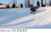 Russian folk - men and women in Russian folk costumes are riding a snow slide. Стоковое видео, видеограф Константин Шишкин / Фотобанк Лори