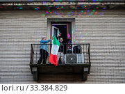 Купить «People plays various musical instruments and objets from their windows and balconies during the musical flash mob to cobact isolation due Coronavirus in Milan ,ITALY-15-03-2020.», фото № 33384829, снято 15 марта 2020 г. (c) age Fotostock / Фотобанк Лори
