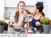 Купить «Smiling girl doing make-up for female friend at table with cosmetics», фото № 33386629, снято 29 августа 2018 г. (c) Яков Филимонов / Фотобанк Лори