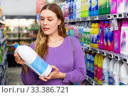 Young woman buying household chemicals or laundry detergent at supermarket. Стоковое фото, фотограф Яков Филимонов / Фотобанк Лори