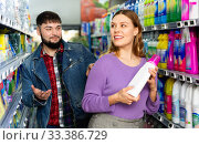 Купить «Portrait of positive young woman and man choosing liquid laundry detergents during shopping at supermarket», фото № 33386729, снято 4 июля 2020 г. (c) Яков Филимонов / Фотобанк Лори