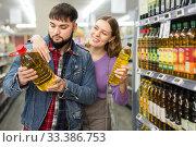Couple shopping oil in food store. Стоковое фото, фотограф Яков Филимонов / Фотобанк Лори