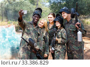 Cheerful group of paintball players in full gear making selfie with smartphone outdoors. Стоковое фото, фотограф Яков Филимонов / Фотобанк Лори