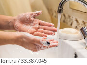 Купить «Person holding his hands with soap foam under water stream, close up view», фото № 33387045, снято 16 марта 2020 г. (c) Кекяляйнен Андрей / Фотобанк Лори