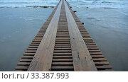 Ускоренная видео съемка волны накатывающие на песчаный берег, причал уходящий в море. Стоковое видео, видеограф Иванов Алексей / Фотобанк Лори
