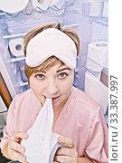 Woman in pajamas eats toilet paper near the fridge filled with wc-paper. Стоковое фото, фотограф Kira_Yan / Фотобанк Лори