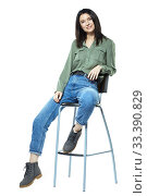 Купить «A young woman in jeans, boots and a khaki shirt is sitting on a high chair. Isolated on white.», фото № 33390829, снято 11 января 2020 г. (c) Serg Zastavkin / Фотобанк Лори
