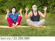 Beautiful athletic mature couple doing gymnastics in medical masks in the park. Стоковое фото, фотограф Акиньшин Владимир / Фотобанк Лори