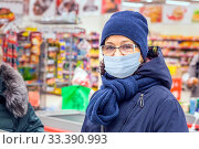 Купить «Russia Samara January 2020: Portrait of a mature woman waiting in line at the checkout counter in a supermarket in a medical mask.», фото № 33390993, снято 11 января 2020 г. (c) Акиньшин Владимир / Фотобанк Лори