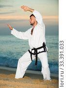 Купить «Adult male doing karate at ocean quay», фото № 33391033, снято 19 июля 2017 г. (c) Яков Филимонов / Фотобанк Лори