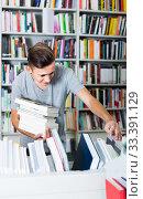 Купить «portrait of boy standing among bookshelves and searching for book in library», фото № 33391129, снято 16 сентября 2016 г. (c) Яков Филимонов / Фотобанк Лори