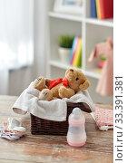Купить «teddy bear toy in basket with baby things on table», фото № 33391381, снято 14 февраля 2019 г. (c) Syda Productions / Фотобанк Лори
