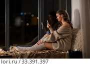 Купить «woman with smartphone and earphones at home», фото № 33391397, снято 19 января 2020 г. (c) Syda Productions / Фотобанк Лори